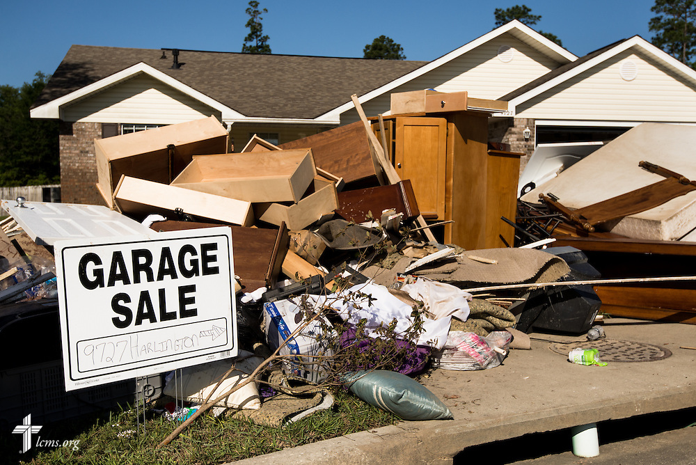 A sign juxtaposes against debris in a damaged neighborhood of Pensacola, Fla., on Saturday, May 3, 2014, after torrential rainfall led to widespread flooding in the area earlier in the week. LCMS Communications/Erik M. Lunsford