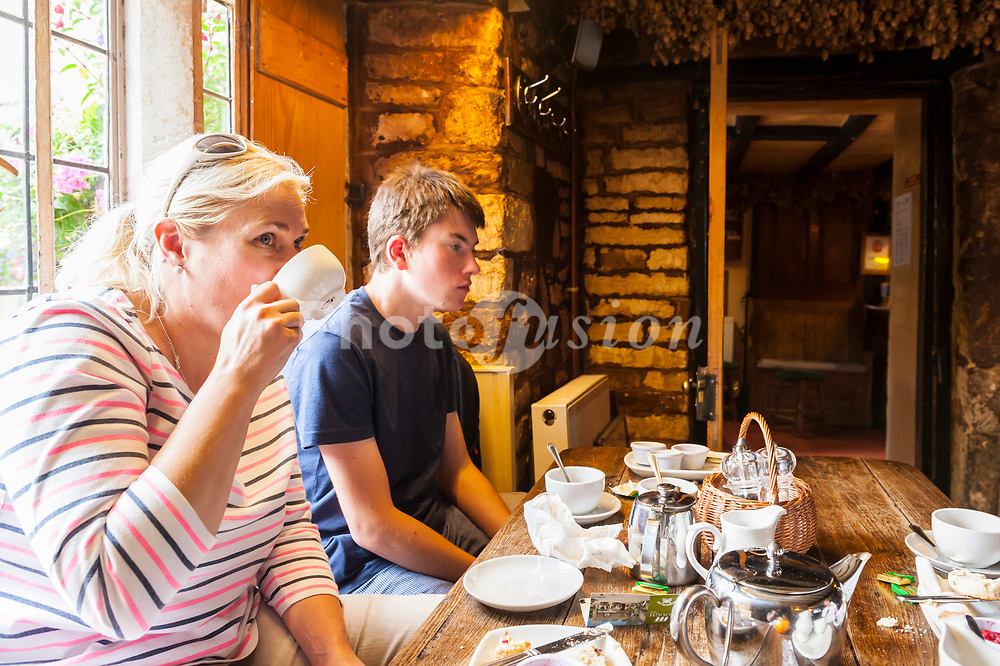 A family enjoy a cream tea at the Plough Inn , <br /> Ford , <br /> Temple Guiting , <br /> Cheltenham , England , Britain , Uk