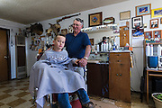 Nelson Cue, owner of Nelson's Barber Shop in Crescent, cuts the hair of CREC member Lukas Bartram of Stillwater.