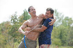 Two men being playful with a garden hose