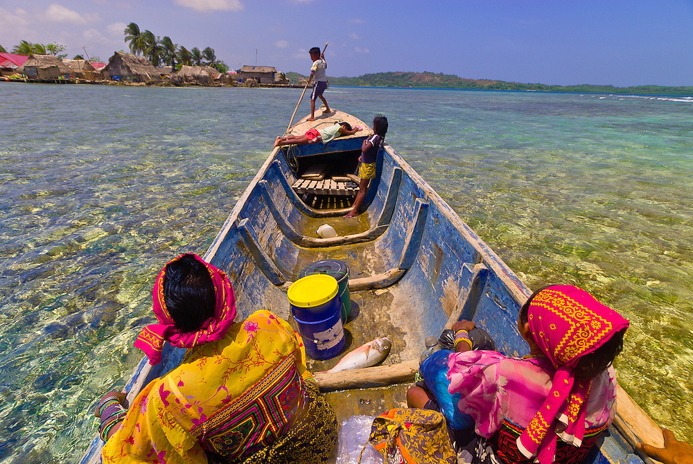 Kuna Indians (women wearing native costumes with Mola embrodery blouses) in their dugout canoe arriving at Corbisky Island, San Blas Islands (Kuna Yala), Caribbean Sea, Panama