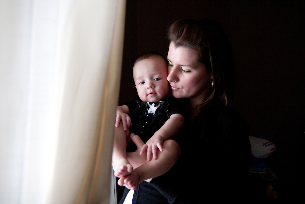 A mother and child are lit up by window light at their home
