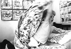 Young child throwing bed clothes around during tantrum,