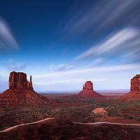 A windy night as clouds rip across the desert sky. A car streaks across the dirt road amongst the Monuments.