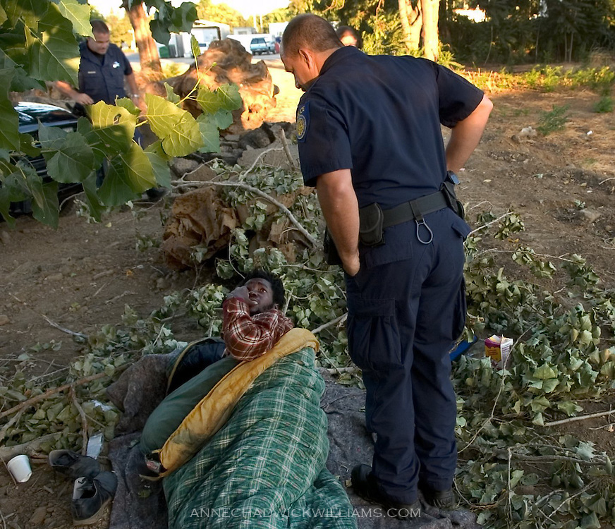 "Sacramento police officer Mike Cooper wakes up Maynard Philips who was sleeping in a field near the Union Gospel Mission in Sacramento, CA on August 4, 2005.  Cooper and Mark Zoulas, back left, acknowledge that their goal is ""to get everyone out of here,"" but it takes longer with some people."