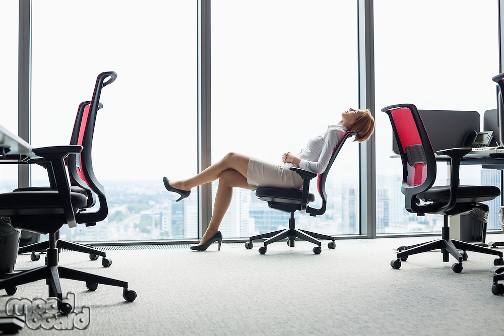 Full length side view of young businesswoman leaning back in chair at office