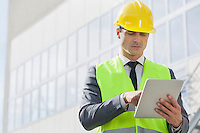 Young male engineer using digital tablet outside industry
