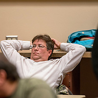 Frank Chapatti stretches while waiting for completion of Executive Session of the McKinley County Schools Board of Education in Gallup Monday.