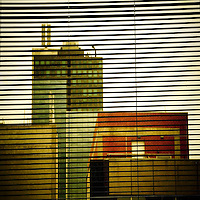 City buildings behind window blinds