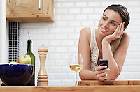 Young woman holding mobile phone leaning on kitchen counter