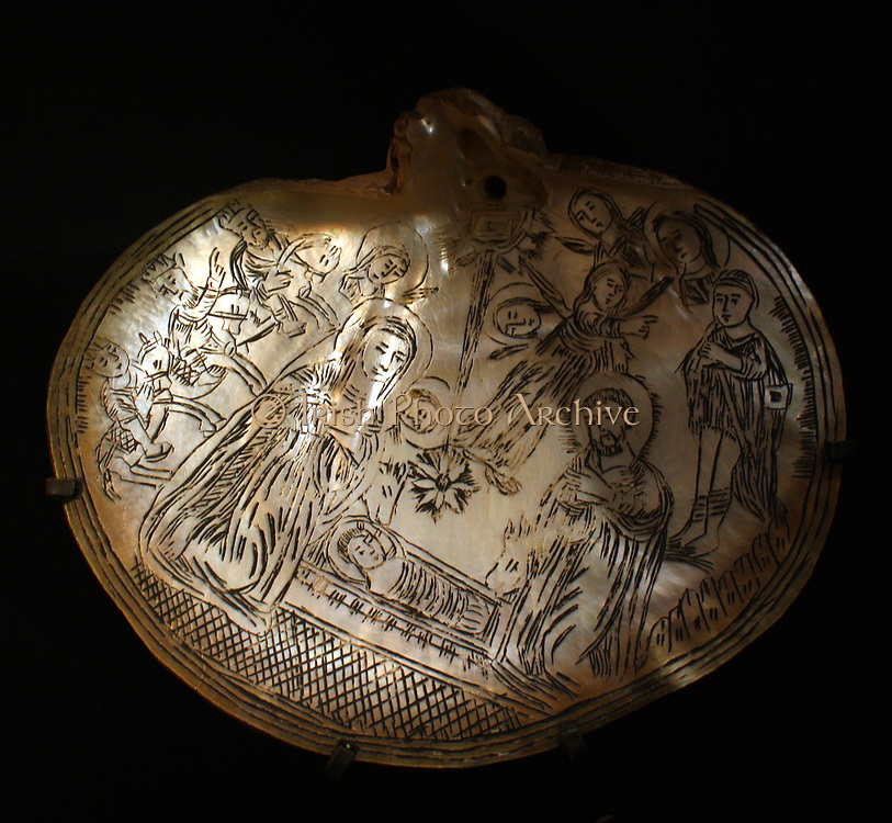 Pearl oyster shells.  Decorated shells were made in the Holy Land from 1700-1900 as souvenirs for pilgrims.  Some have incised decoration closely resembling engravings on paper, which probably served as models. Adoration of the infant Christ.