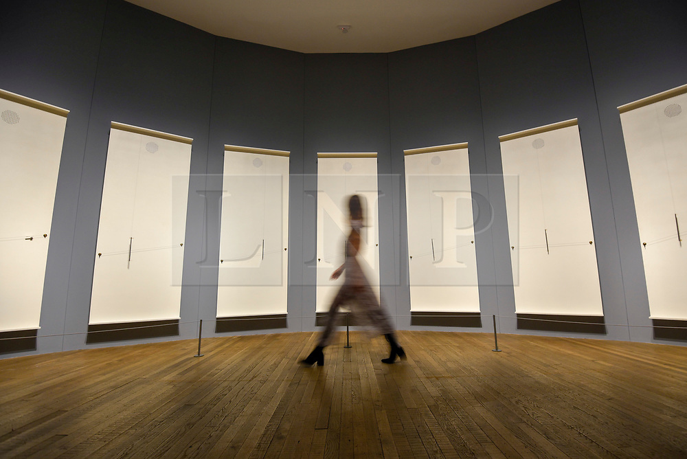 "© Licensed to London News Pictures. 02/07/2019. LONDON, UK.  A visitor walks by ""Musicals"", 1985-2004, by Takis.  Preview of a new display by the Greek sculptor Takis at Tate Modern.  The retrospective features over 80 works in Takis' largest exhibition in the UK to date and combines works involving magnetism, light and sound.  The show runs 3 July to 27 October..  Photo credit: Stephen Chung/LNP"