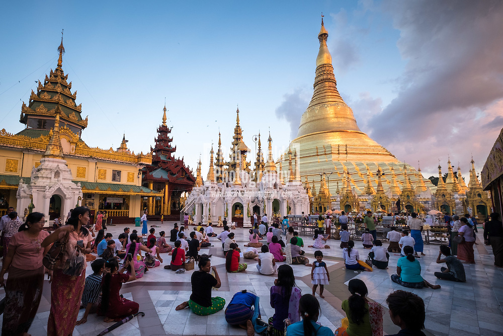 People praying during sunset at the Shwedagon Pagoda in Yangon, Myanmar.