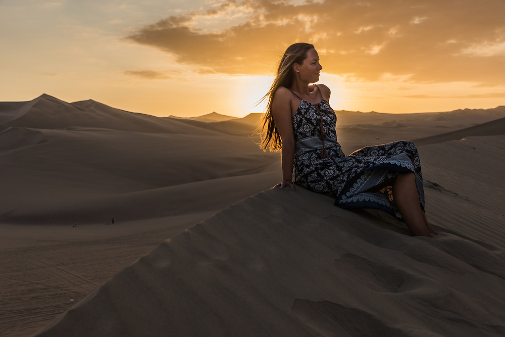 Woman sits on top of a sanddune at sunset near the town of Huacachina, Peru.