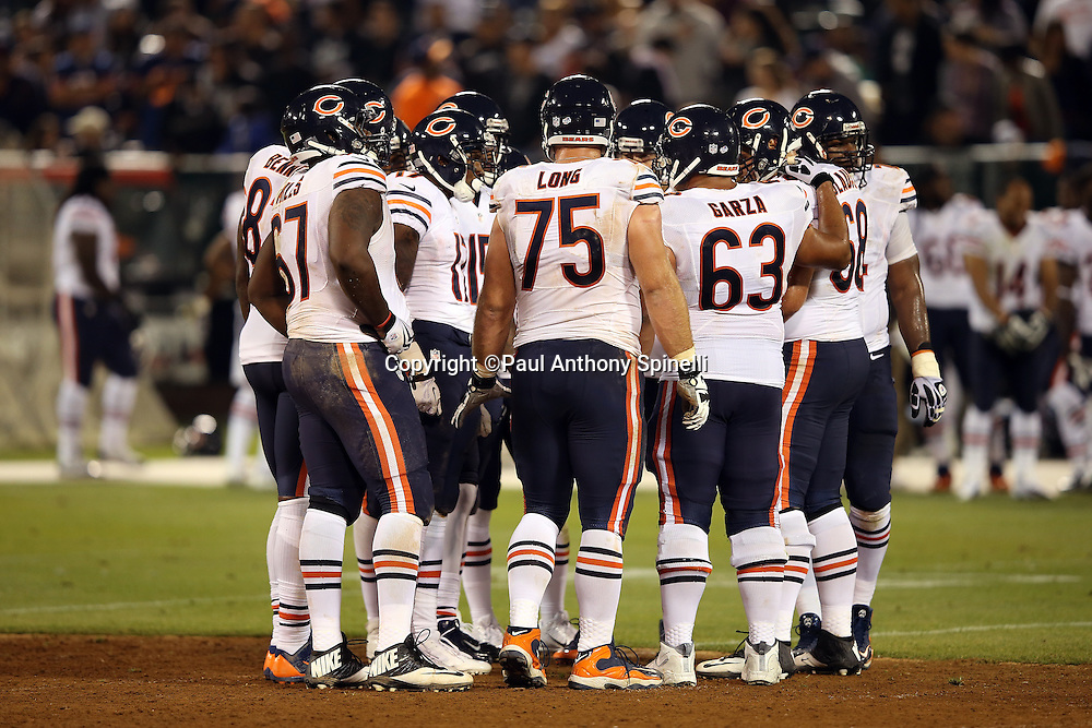 Chicago Bears offensive guard Kyle Long (75) and his offensive teammates huddle to call a play during the NFL preseason week 3 football game against the Oakland Raiders on Friday, Aug. 23, 2013 in Oakland, Calif. The Bears won the game 34-26. ©Paul Anthony Spinelli