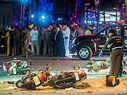 17 AUGUST 2015 - BANGKOK, THAILAND:  A Thai police officer looks at one of the victims of the explosion at Erawan Shrine Monday. An explosion at Erawan Shrine, a popular tourist attraction and important religious shrine, in the heart of the Bangkok shopping district killed at least 19 people and injured more than 120 others, mostly foreign tourists, during the Monday evening rush hour. Twelve of the dead were killed at the scene. Thai police said an Improvised Explosive Device (IED) was detonated at 18.55. Police said the bomb was made of more than six pounds of TNT stuffed in a pipe and wrapped with white cloth. Its destructive radius was estimated at 100 meters. The Bangkok government announced that public schools would be closed Tuesday as a precaution.       PHOTO BY JACK KURTZ