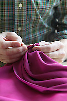 Tailor sewing fabric close up of hands mid section