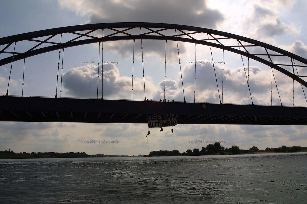 Activists protest against new planned roads hanging down from a bridge. Aktivisten der Umweltschutzgruppe Robin Wood haben sich von der Dömitzer Elbbrücke abgeseilt. Mit ihrem Protest richten sie sich gegen die Baupläne der Autobahn A39 und A14.