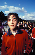 Teenager in red two-stripe shell suit, Istanbul, Turkey, 2000s.