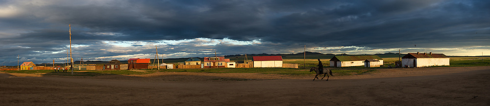 A lone horseman rides into town at sunset in the town of Bayaan Ovoo, Mongolia