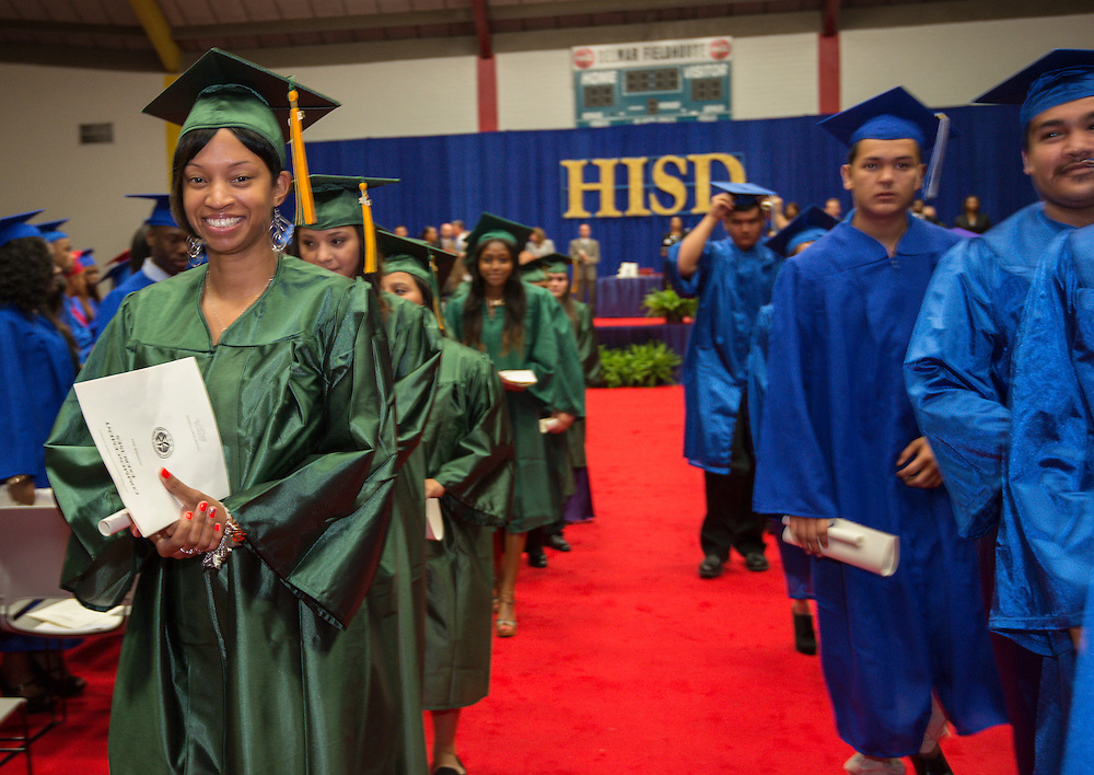 Samiya Jene'e Savannah, left, walks out following graduation ceremonies at Delmar Fieldhouse, August 17, 2013. Savannah completed her course work at Sharpstown High School in 1996 but did not pass the standard exam required to graduate. She eventually got a GED and went to college. She decided to complete the required test and walk at graduation to have a diploma like her oldest son.
