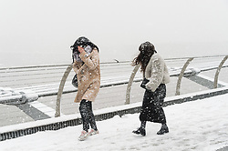 © Licensed to London News Pictures. 28/02/2018. London, UK. Tourists walk across Millennium Bridge as heavy snowfall hits central London at lunchtime. The cold spell named The Beast From The East is due to last a few days. Photo credit: Ray Tang/LNP