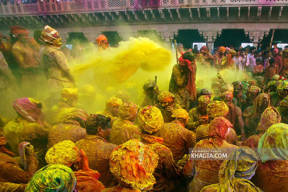 A man tries to protect himself from the yellow colored powder being thrown at him while celebrating, Holi, 'the festival of colors' in Nand Gaon Village of India.<br /> <br /> People sit together and sing and abuse each other in braj language while others throw colored powder and water on them.