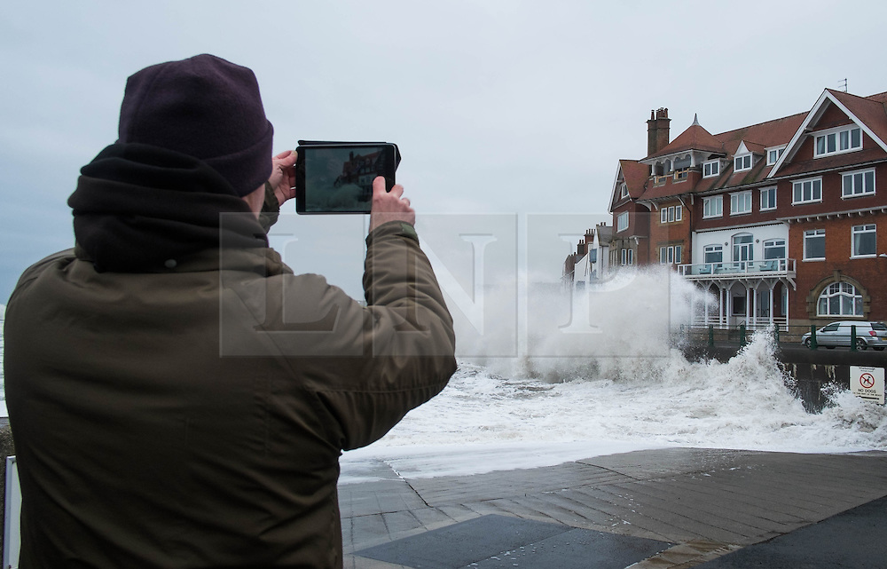 © Licensed to London News Pictures. <br /> 21/03/2015. <br /> <br /> Sandsend, North Yorkshire.<br /> <br /> A member of the public takes a picture as a huge wave crashes against the sea wall at Sandsend in North Yorkshire. The exceptionally high Spring tides were created by the moon's 18-year cycle.<br /> <br /> Photo credit : Ian Forsyth/LNP