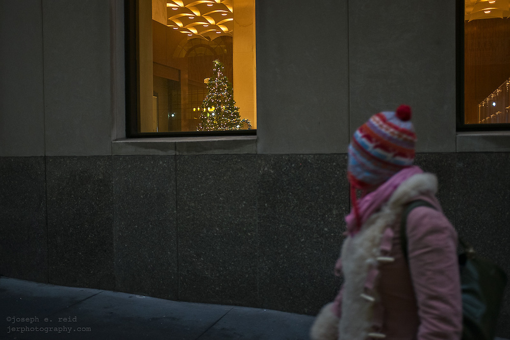 Woman walking past Christmas tree seen through bank window, New York, NY, US