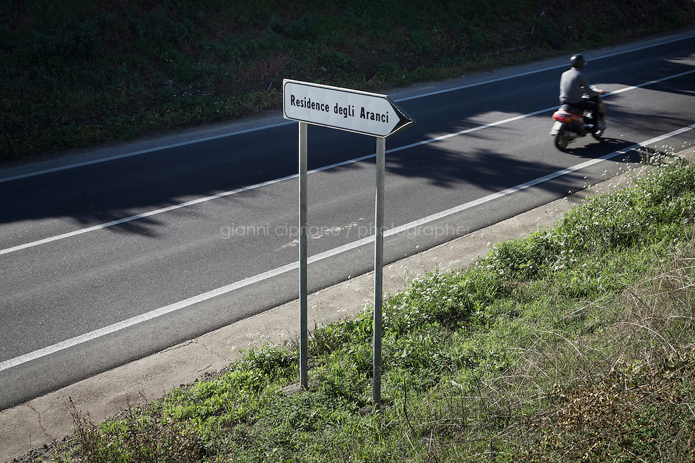MINEO, ITALY - 14 NOVEMBER 2014: a road sign for the nearby CARA (Accommodation Centre for Asylum Seekers) in Mineo where approximately 4,000 asylum seekers live, in Mineo, Italy, on November 14th 2014.<br /> <br /> By law, asylum-seekers can be held for 35 days in a CARA. In reality, the average stay is closer to a year.The Cara is located at the &quot;Residence degli Aranci&quot; (Residence of the Oranges), a small town built to accomodate the families of US soldiers operating at the Naval Air Station of Sigonella 40km away. Since 2011 the &quot;Residence degli Aranci&quot; hosts the Accommodation Center for Asylum Seekers, which has since then hosted more than 12,000 seekers of 47 nationalities and over 200 ethnic groups. The CARA of Mineo includes 404 houses. Each house hosts from 7 to 11 asylum seekers.