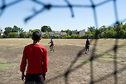 (L to R) Yogesh Acharya (13), Roshan Biswa (13) and Roshan Diyali (13) play soccer across from their homes in the Ivy Apartments where Thomas E. Duncan, the first confirmed Ebola virus patient in the United States, was staying with family in Dallas, Texas on October 4, 2014. Duncan is now being treated at Texas Health Presbyterian Hospital Dallas while members of his family have been isolated in the apartment. (Cooper Neill for The New York Times)
