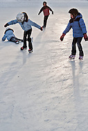 A group of children skating on frozen river in Calgary together