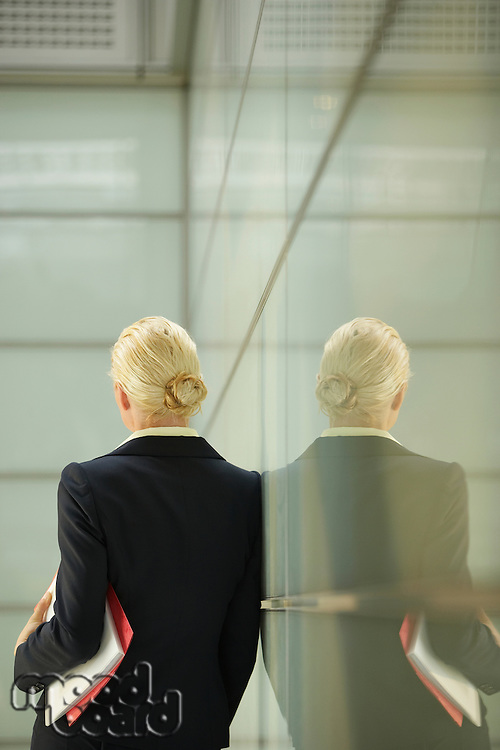 Businesswoman Leaning Against Glass Partition