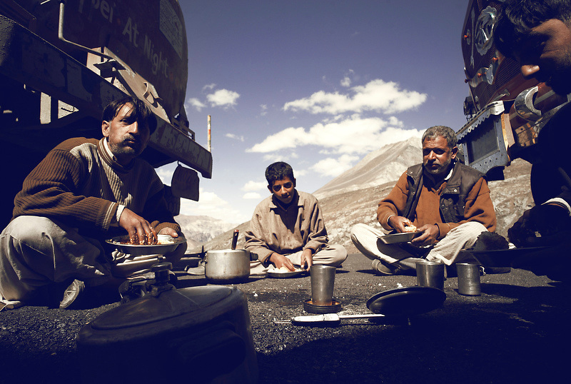 While road work is undertaken on the road ahead, truck drivers eat lunch on the road above Keylong, capital of the Lawaul Bhage region, India on Sep 9, 2007.