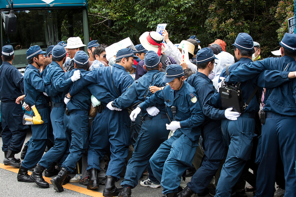OKINAWA, JAPAN - SEPTEMBER 14 : Anti U.S base protesters is seen being guarded by police after blocking the trucks to protest against the construction of helipads in front of the gate of U.S. military's Northern Training Area in the village of Higashi, Takae, Okinawa Prefecture, Japan on September 14, 2016. The Japanese government is allowing the use of its own Japan Air Self-Defense Force military helicopters Boeing CH-47 to get construction heavy equipments past the protesters on Tuesday, September 13 in order to speed up completion of six new helipads to be use by U.S Military.  (Photo by Richard Atrero de Guzman/NURPhoto)