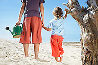 Two boys (7-12) with watering can standing by dead tree on beach