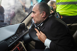© Licensed to London News Pictures. 07/10/2019. London, UK. An Extinction Rebellion protester uses a bicycle lock to lock his neck to the steering wheel of a hearse in Trafalgar Square. Two weeks of action are planned at various locations around Westminster as part of a coordinated protest to call on government to act on climate change. Photo credit: Rob Pinney/LNP
