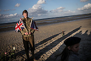 Reenactors gathering on Utah Beach for a ceremony onoring the WWII women posing with the French, the American, the Canadian and the British flag