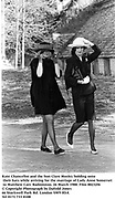 Kate Chancellor and the hon Clare Mosley holding onto their hats while arriving for the marriage of Lady Anne Somerset to Matthew Carr. Badminton. 26 March 1988. Film 88232f6<br />