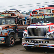 Two chicken buses behind the Mercado Municipal (town market) in Antigua, Guatemala. From this extensive central bus interchange the routes radiate out across Guatemala. Often brightly painted, the chicken buses are retrofitted American school buses and provide a cheap mode of transport throughout the country.