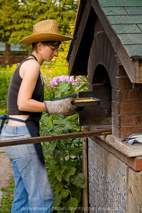 A woman wearing a straw cowboy hat and well-used oven mitts places a pan into an outdoor, wood-fired bread oven for communal baking.