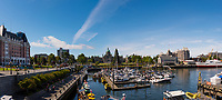 The Inner Harbour of Victoria, BC is full of boats and busy with travellers on a sunny summer day.