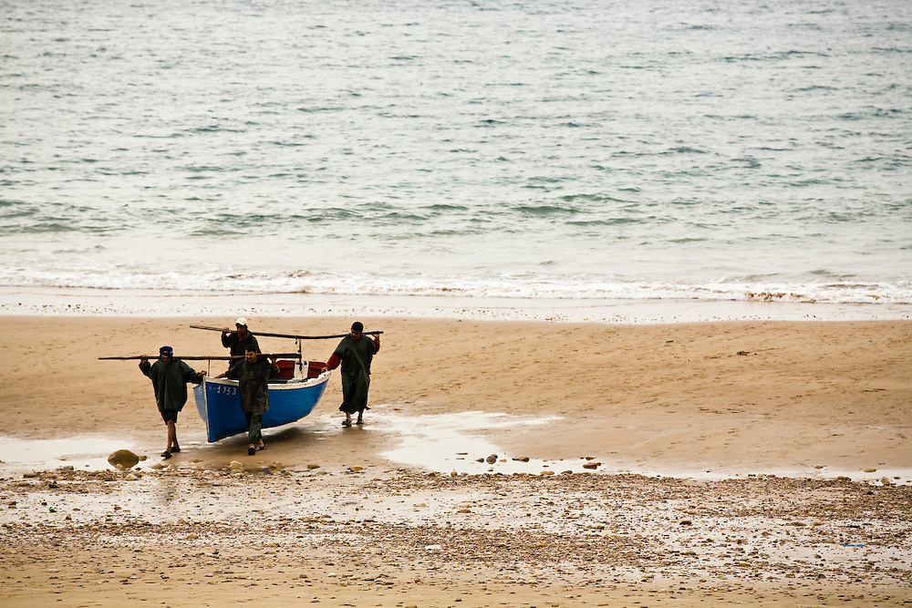 Fisherman carry their boats on the beach at Taghazout on the Atlantic Coast of Morocco. This is a traditional fishing community north of Agadir.