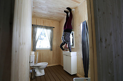 EDITORS NOTE:<br /> THIS IMAGE HAS BEEN ROTATE 180 DEGREES An employee holds onto the sink in the bathroom in 'The Upside Down House', a zero-gravity illusion experience, in The Triangle in Bournemouth, Dorset.