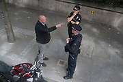 The rider of a motorbike who has been stopped by City of London Police, talks to officers at the roadside in the Square Mile, the capital's financial district, on 6th August 2020, in London, England.