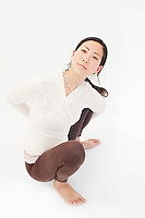 Woman in yoga asana variation half-bound malasana pose.<br /> :::<br /> Twists penetrate deep into the body's core, offering potent benefits to the muscles and organs of the torso while encouraging the breath to grow deep and full. Practicing these postures regularly can create a suppleness and freedom in your spine that in turn brings a spring to your step. Like any yoga posture, though, twists should be practiced with mindfulness and care.&quot;<br /> -Claudia Cummins Yoga