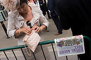 CLose-up of a punter with her handbag and racing betting newspaper during the annual Royal Ascot horseracing festival in Berkshire, England. Royal Ascot is one of Europe's most famous race meetings, and dates back to 1711. Queen Elizabeth and various members of the British Royal Family attend. Held every June, it's one of the main dates on the English sporting calendar and summer social season. Over 300,000 people make the annual visit to Berkshire during Royal Ascot week, making this Europe's best-attended race meeting with over £3m prize money to be won.