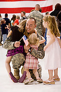 "30 MARCH 2008 -- PHOENIX, AZ: Arizona National Guard Lt. DENNIS CHAMBERLAIN, hugs his daughters, CHLOE CHAMBERLAIN, 7, KACI CHAMBERLAIN, 4, and CAMRYN CHAMBERLAIN, 2, after he returned to Phoenix Sunday from a year long deployment to Afghanistan. Chamberlain, a platoon commander in D Company, commanded the rescue of US Senators Chuck Hagel, John Kerry and Joe Lieberman after their helicopter made a hard landing on a mountain top during a blizzard in Afghanistan in February 2007. About 250 members of the Arizona Army National Guard's 158th Infantry Battalion returned to Phoenix, AZ, from a year long deployment in Afghanistan Sunday. The unit, also known as the ""Bushmasters"" from their service in World War II, was part of the largest single-unit deployment of the Arizona National Guard since the second World War. Two members of the battalion were killed in action during their deployment. The battalion, a combat unit, engaged in counter insurgency operations through out their deployment. Photo by Jack Kurtz / ZUMA Press"