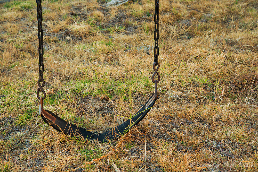 Empty swing on a collapsing swingset, frozen in time on dying grass at an abandoned playground at Point Molate in Richmond, California.