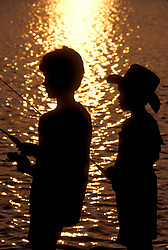 Stock photo of two young boys fishing at sunset